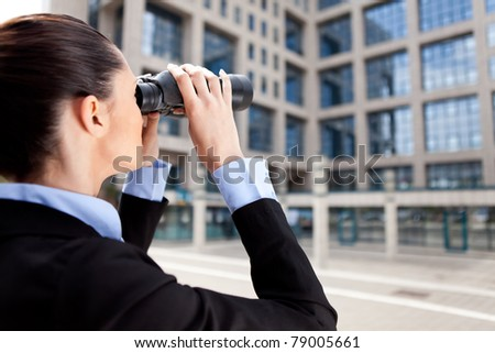 businesswoman looking through binoculars in competition building