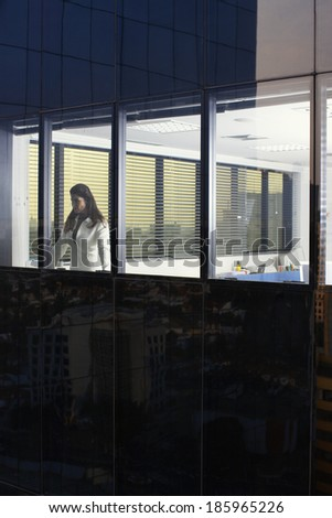 Businesswoman looking through office window (exterior view)