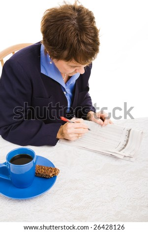 Businesswoman looking through the newspaper researching possible jobs.  Isolated on white.