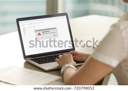 Businesswoman looks at laptop screen with Operation Error message. Entrepreneur experienced system failure during workflow. Computer system crash, software failure, malware. Rear view over shoulder.