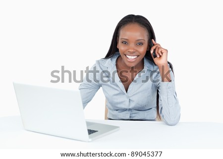 Businesswoman making a phone call while using a laptop against a white background