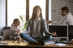 Businesswoman meditating at workplace, avoiding problem at work, ignoring annoying colleagues, female employee, intern sitting with closed eyes at office desk, keep calm in stressed situation