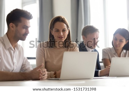 Businesswoman mentor coach teaching new male employee, looking at laptop screen, colleagues working on online project together, analyzing statistics, discussing strategy at group meeting in office