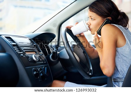 Businesswoman multitasking while driving, drinking coffee and talking on the phone