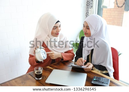 businesswoman muslim customer showing alarm clock and confirm seller to confirm some task not to be late with computer and coffee cup on wood desk #1336296545