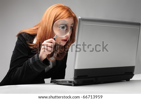 Businesswoman observing a laptop with a magnifying glass