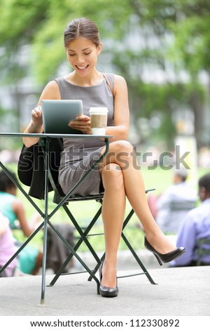 Businesswoman on break in park. Young professional business woman using tablet computer in Bryant Park, New York City, USA. Mixed race Asian Chinese / Caucasian female model.