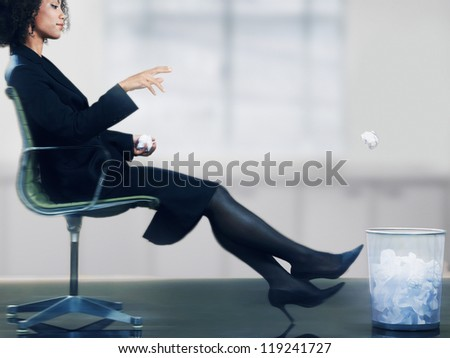 Businesswoman on chair throwing paper ball into dustbin