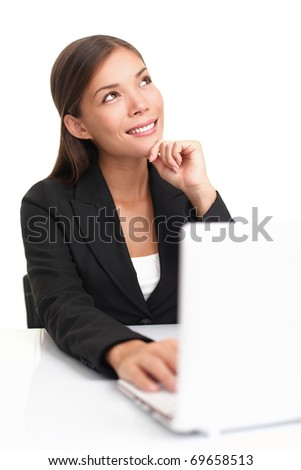 Businesswoman on laptop thinking looking up at copy space. Beautiful young business woman sitting by table isolated on white background.