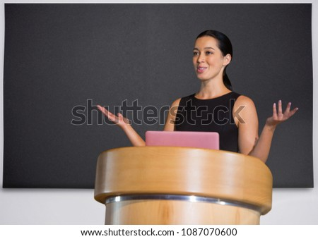 Businesswoman on podium speaking at conference with board