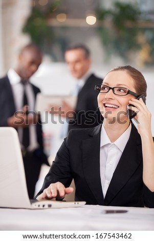Businesswoman on the phone. Cheerful young woman in formalwear sitting at the table and talking on the mobile phone while two colleagues standing on background