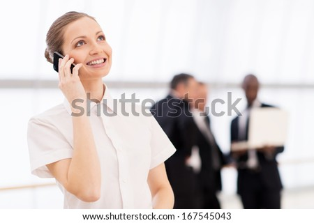 Businesswoman on the phone. Cheerful young woman in white shirt talking on the mobile phone and smiling while his colleagues standing on background