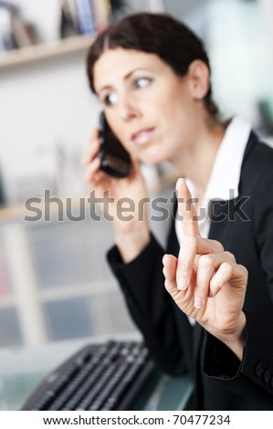 Businesswoman on the phone signaling to someone to hold on.