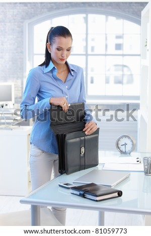 Businesswoman opening briefcase, standing at office desk.?