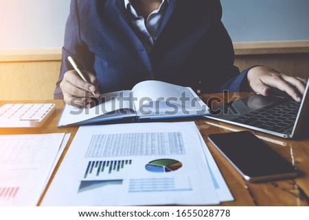 Businesswoman or Accountant hands holding pen with laptop , account and saving concept.