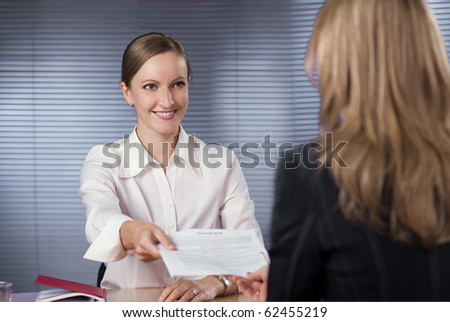 Businesswoman (or notary public) holding pen pointing at signature place on a contract document to woman
