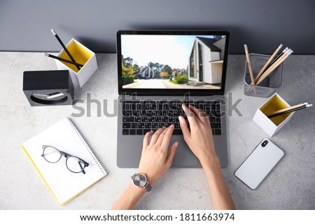 Businesswoman or real estate agent looking through online property portfolio, top view