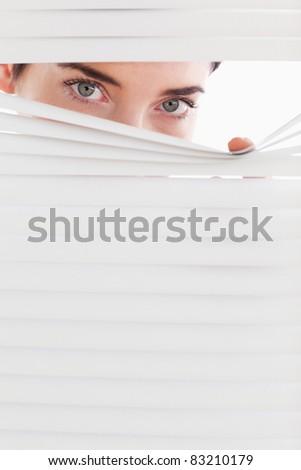 Businesswoman peeking through a venetian blind in an office