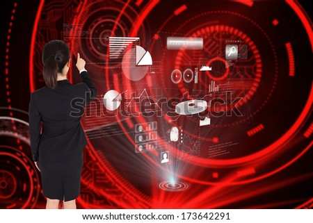 Businesswoman pointing against shiny red circles on black background