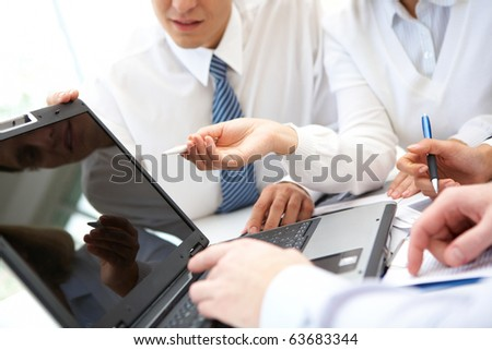 Businesswoman pointing at lcd screen while explaining something at meeting