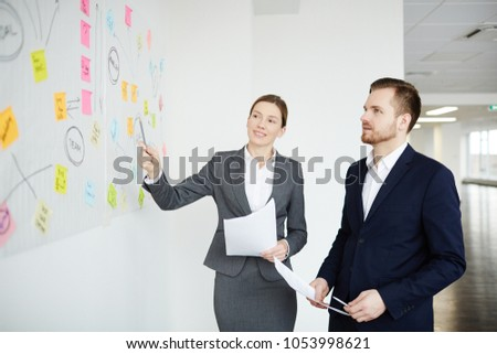 Businesswoman pointing at one of notepapers on whiteboard while discussing working points with colleague