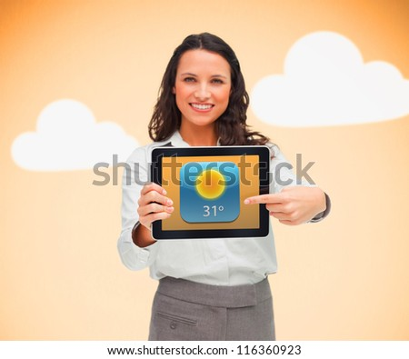 Businesswoman pointing to weather app symbol on tablet on orange cloud background - stock photo