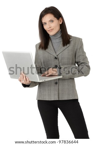 Businesswoman portrait, standing with laptop computer, smiling at camera confidently.