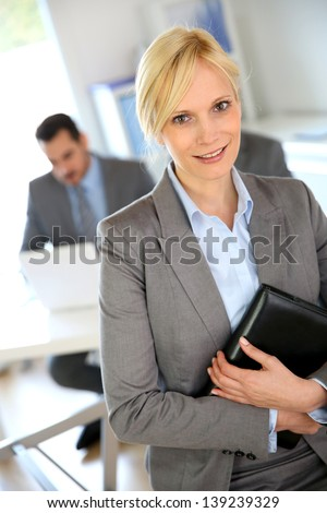 Businesswoman portrait with group in background