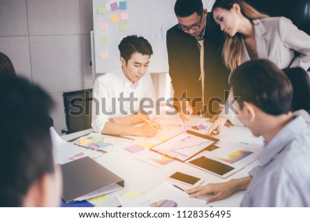 Businesswoman presenting to colleagues at a meeting.Successful team leader and business owner leading informal in-house business meeting. Businessman working on laptop in foreground. #1128356495