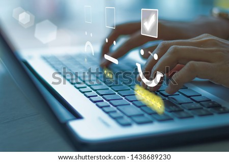 Businesswoman pressing face emoticon on the keyboard laptop .Customer service evaluation concept. Blue tone #1438689230