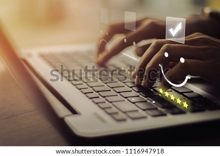 Businesswoman pressing smiley on keyboard laptop .Customer service evaluation concept.  Stockfoto ©