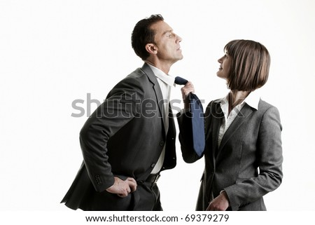 Businesswoman pulling her colleague from his tie