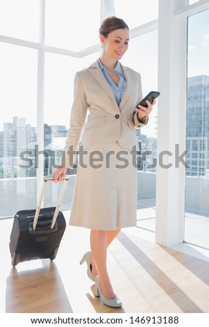 Businesswoman pulling her suitcase and checking her phone in bright office