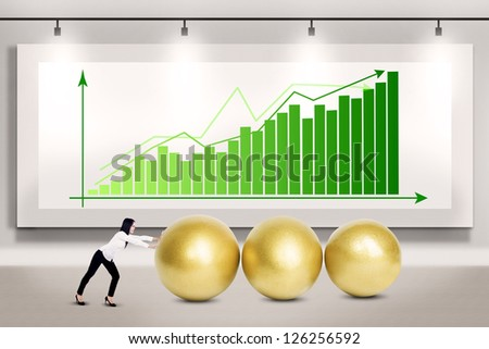 Businesswoman pushing three golden eggs on bar chart background