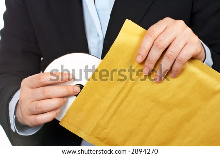 Businesswoman put dvd disc on the envelope over a white background - stock photo