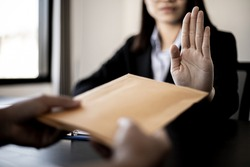 Businesswoman raised her hand to deny accepting a bribe from a business partner, a brown envelope containing a large number of dollar bills as money for bribery, a corruption concept.