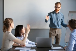 Businesswoman raising hand up at meeting asking presenter team leader, mentor or coach answering questions during seminar or corporate office training, business education and knowledge concept