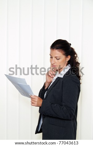 Businesswoman reading a letter in the office. Message from the attorney or tax office.