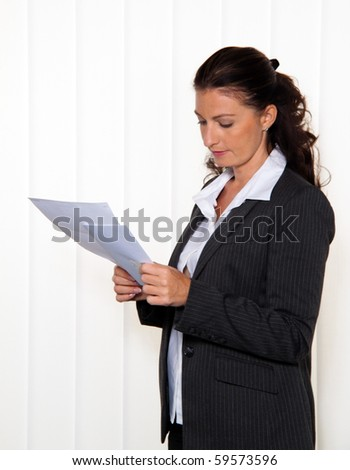 Businesswoman reading a letter in the office. News of the lawyer or tax office.