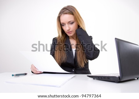 Businesswoman reading contract at his work office sitting near laptop