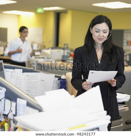 Businesswoman reading paper in office - stock photo