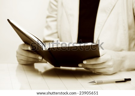 Businesswoman reading the accounting ledger.