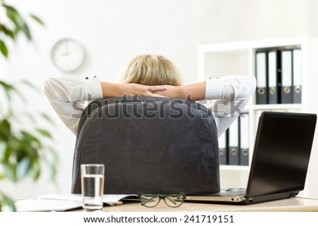 Businesswoman relaxing in office sitting back in chair with hands behind neck