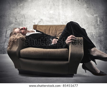 Businesswoman relaxing on an armchair - stock photo