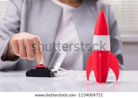 Businesswoman's Hand Launching Rocket By Pressing Red Button