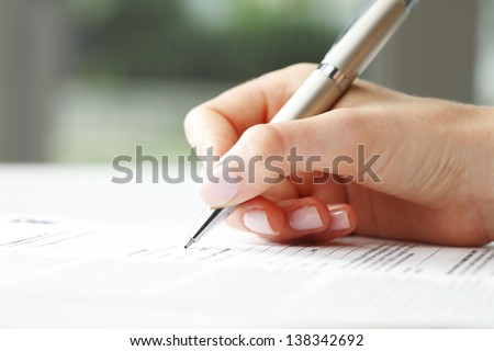 Photo of  Businesswoman's hand with pen completing personal information on a form