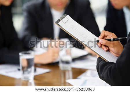businesswoman's hand writing with other business people in background #36230863