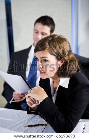 Businesswoman, 40s, watching presentation and with male colleague sitting behind, focus on woman