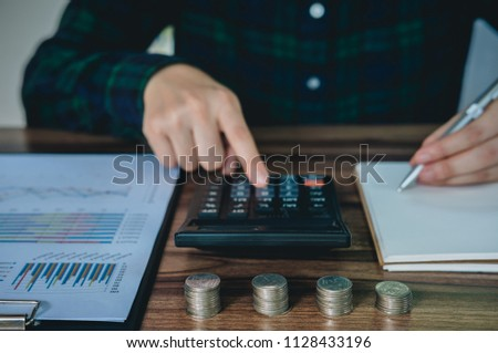Businesswoman saving money and analyzing financial accounts on desk.