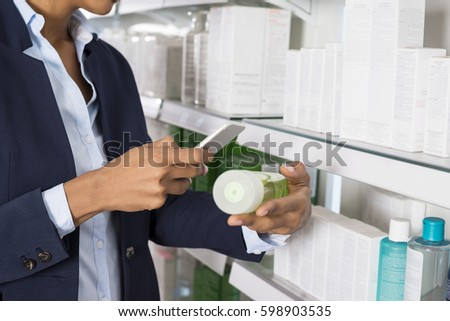 Businesswoman Scanning Product's Barcode Through Smart Phone
